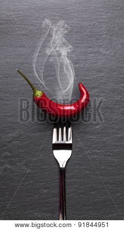 steaming red chili pepper with a black graphite background
