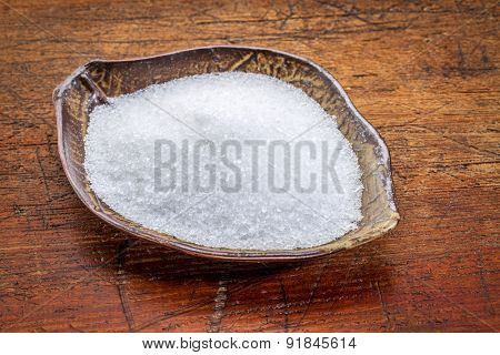 Epsom salts (Magnesium sulfate) in a leaf shaped ceramic bowl against rustic wood - relaxing bath concept