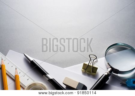 Office Supplies Scattered On Grey Desk