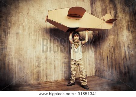 Cute dreamer boy playing with a cardboard airplane. Childhood. Fantasy, imagination. Retro style. poster