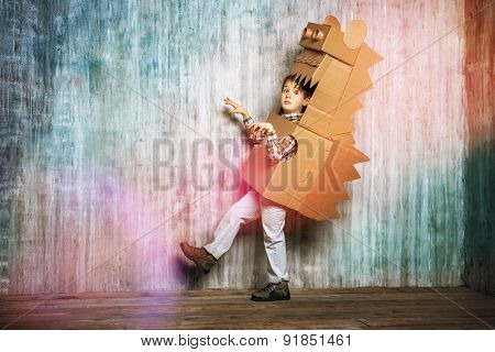 Little dreamer boy playing with a cardboard dragon, dinosaur. Childhood. Fantasy, imagination. poster