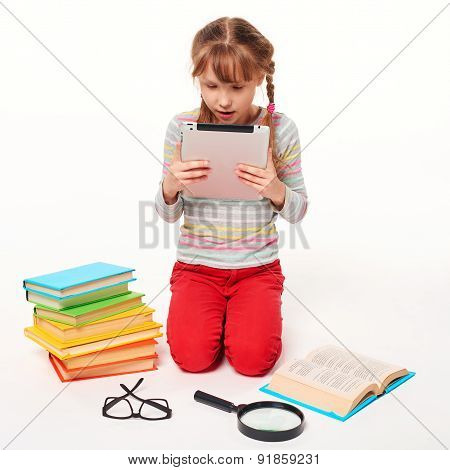 Girl with a lot of books reading digital tablet