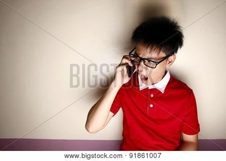 Angry Teenage kid talking on a smartphone