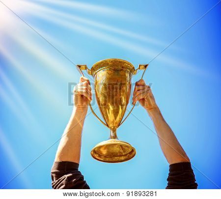a man holding up a gold trophy cup as a winner in a competition (SHALLOW DOF on trophy) generic text