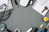 High Angle View of Office Supplies with Mac Computer Keyboard and Mouse Scattered Around Grey Desk Surface with Copy Space in Center poster