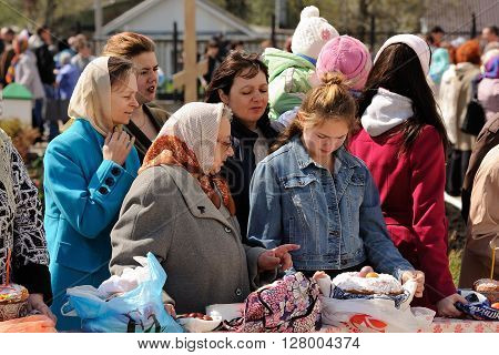 Orel Russia - April 30 2016: Paschal blessing of Easter baskets in Orthodox church. Women and girl waiting for kulich and eggs blessing closeup