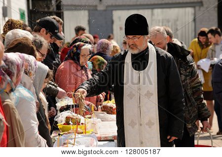 Orel Russia - April 30 2016: Paschal blessing of Easter baskets in Orthodox church. Priest sprinkling holy water on kulichi horizontal
