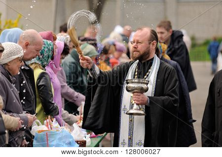 Orel Russia - April 30 2016: Paschal blessing of Easter baskets in Orthodox church. Priest blessing people with holy water closeup