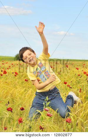 happy boy jumping on field