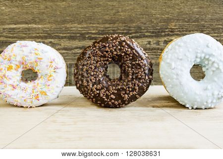 Three donuts on a wooden surface close up