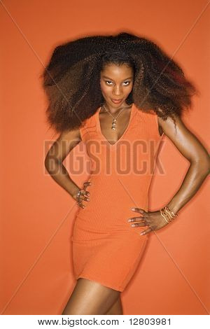 Sexy young African-American adult woman with big hair on orange background wearing dress and looking seductively at viewer.