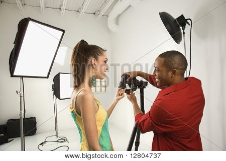 Young African American male adult and Caucasian young female adult previewing image on digital camera.