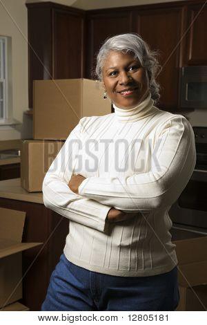Retrato de mediana edad mujer afroamericana en cocina con cajas de mudanza.