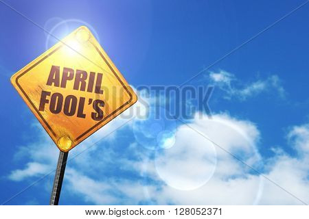Yellow road sign with a blue sky and white clouds: april fool's