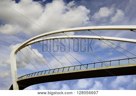 pedestrian bridge against the sky with clouds