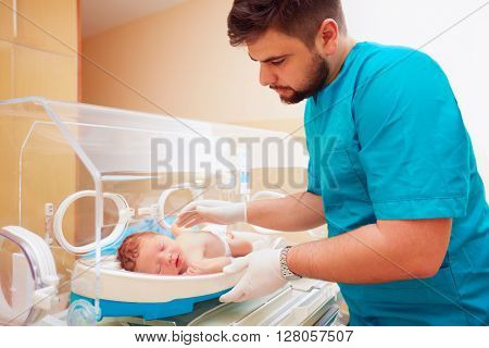 Young Adult Man Taking Care Of Newborn Baby In Infant Incubator