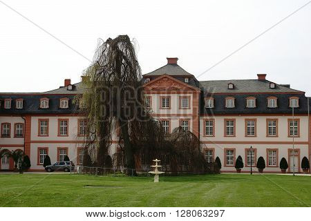 WIESBADEN, GERMANY - APRIL 21, 2016: The rear view of the castle Biebrich at the park with a weeping willow in front of the facade on April 21, 2016 in Wiesbaden.