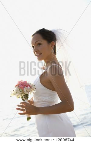 Young adult female Caucasian bride holding bouquet on beach.