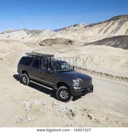 Four wheel drive truck on dirt road in barren landscape in Death Valley National Park.