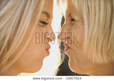 White mother and daughter face to face squinting at each other.