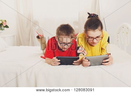 Two children, siblings on parents' bed at morning with tablets. Brother and sister play computer games. Siblings and gadgets. Children in glasses.