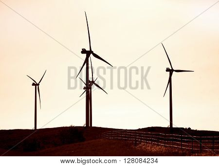 Sihouette of wind turbines in the hills of Southwest Oklahoma .