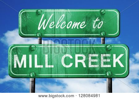 mill creek vintage green road sign with blue sky background