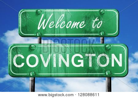 covington vintage green road sign with blue sky background