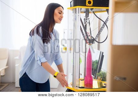 Look how it works. Pleasant cheerful beautiful woman standing near 3d printer and looking at it while being involved in work