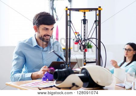 Find inspiration in work.  Positive content smiling man using tablet and working with 3d printer while his colleague resting in the background