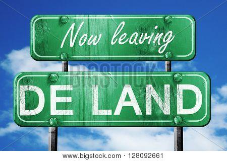 Leaving de land, green vintage road sign with rough lettering