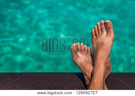 A shot of relaxation gesture with crossed legs overlooking the ocean.