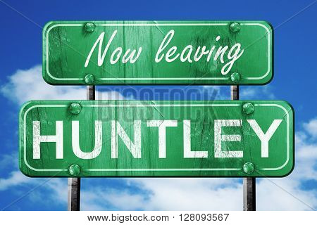 Leaving huntley, green vintage road sign with rough lettering