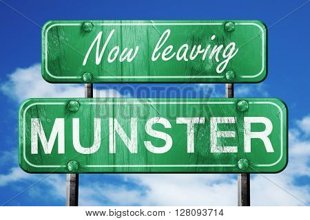Leaving munster, green vintage road sign with rough lettering