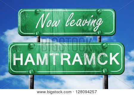 Leaving hamtrack, green vintage road sign with rough lettering