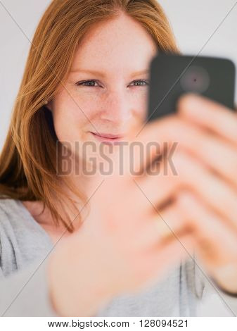 Smiling young woman looks at a smartphone - making a selfie or chatting with video.