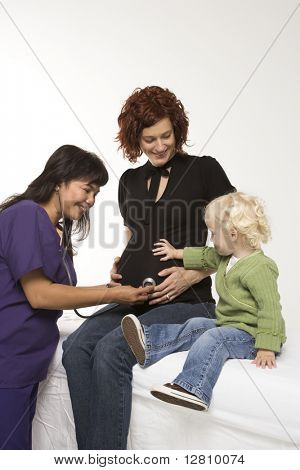 Nurse holding stethoscope on Caucasian pregnant woman's belly.
