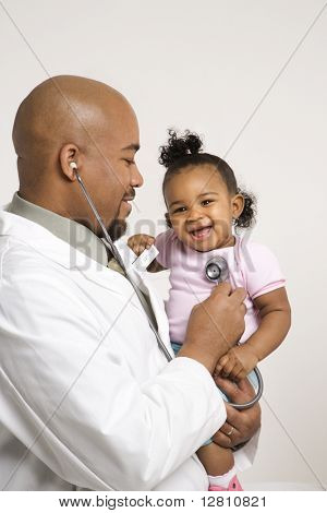 African-American male pediatrician holding and examinating baby girl with stethoscope.