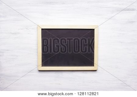Top view of empty chalkboard with copyspace on white wooden table.