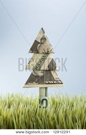 Studio shot of origami tree made from a twenty dollar bill placed in grass.