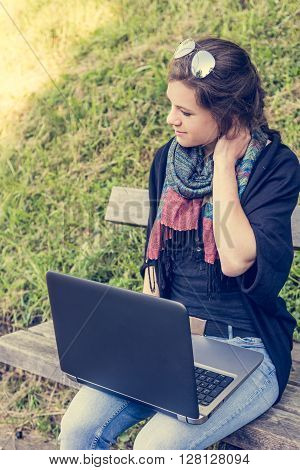 Young woman rubbing her neck while working on a laptop. Millenial working in a park.