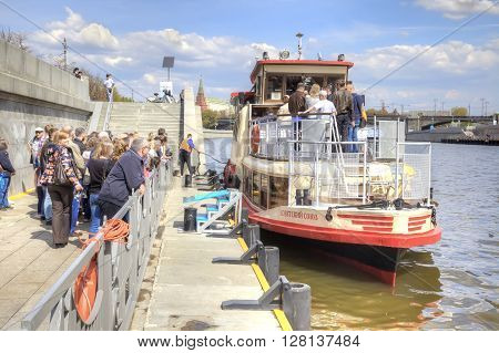 MOSCOW RUSSIA - May 02.2016: People stand on moorage in expectant of landing on an excursion cutter