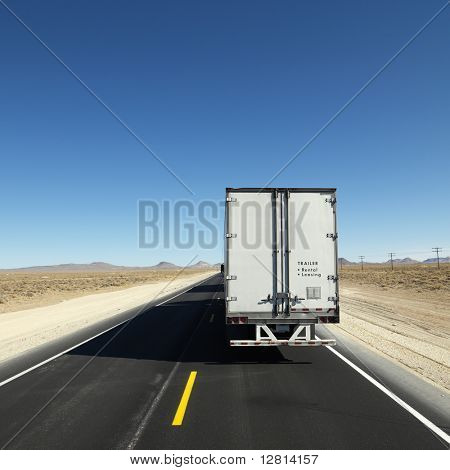 Back view of semi truck traveling down highway towards horizon under clear blue sky.