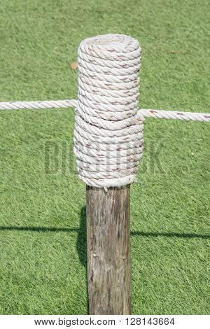 Rope tired in wooden pole with green grass background.