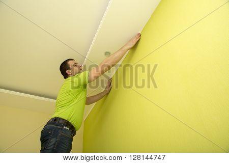 Man constructor renovates room interior with a plastic molding