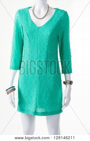 Turquoise dress and accessories. Mannequin with clothing and accessories. V-neck dress with classic watch. Fresh colors of summer.
