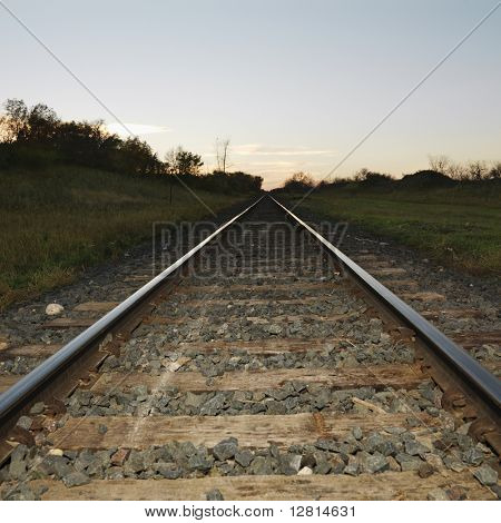 Low angle diminishing view of railroad tracks in rural setting at dusk.