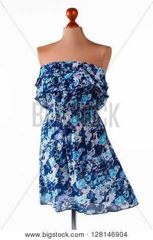 Casual blue strapless dress. Floral dress on armless mannequin. Girl's clothing of light material. New collection of summer clothes.