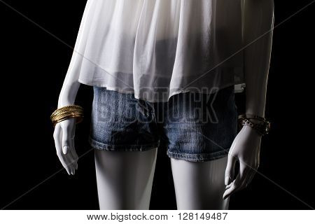 Denim shorts and white top. Female mannequin in denim shorts. Woman's summer shorts and accessories. Seasonal sale of clothes.
