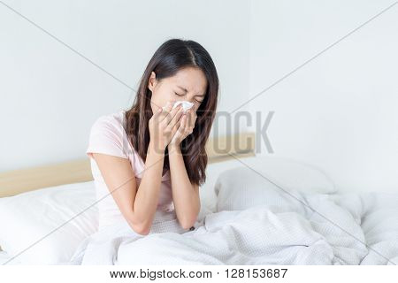 Sick woman blowing lying on her bed at home